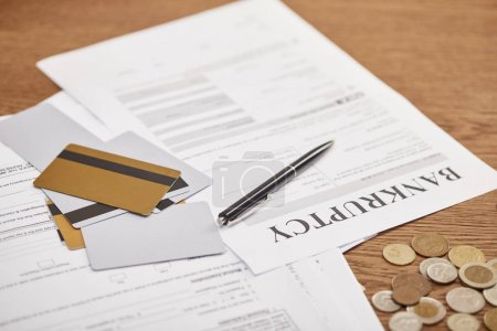 Photo for Bankruptcy form among documents, credit cards and coins on wooden table - Royalty Free Image