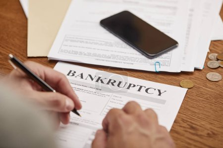 Photo for Partial view of businessman filling in bankruptcy form at wooden table with smartphone - Royalty Free Image