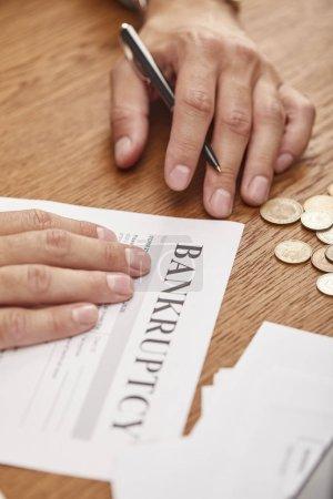 Photo pour Vue partielle de remplissage d'homme d'affaires dans le formulaire de faillite à la table en bois avec des pièces de monnaie - image libre de droit