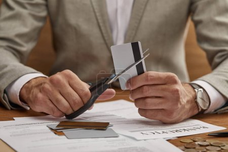 Photo for Partial view of businessman in suit cutting credit card with scissors at wooden table - Royalty Free Image