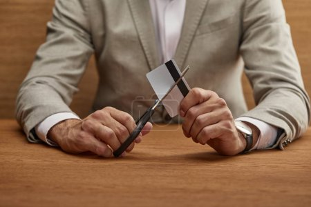 Photo for Cropped view of businessman in suit cutting credit card with scissors at wooden table - Royalty Free Image