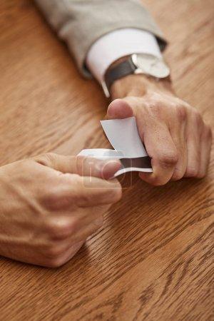 Photo pour Vue partielle de l'homme d'affaires cassant la carte de crédit à la table en bois - image libre de droit