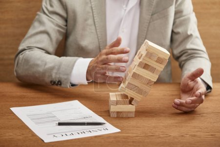 Photo for Partial view of businessman in suit breaking tower made of wooden blocks near bankruptcy form - Royalty Free Image