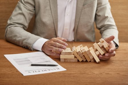 Photo for Partial view of businessman in suit holding fallen tower made of wooden blocks near bankruptcy form - Royalty Free Image