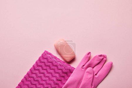 Photo pour Vue du haut du chiffon rose, gant en caoutchouc et savon sur fond rose - image libre de droit