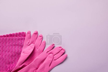 Photo for Top view of pink rag, rubber gloves on purple background - Royalty Free Image