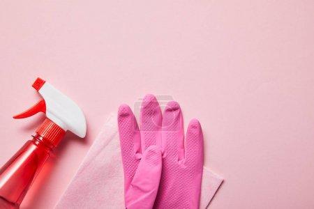 Photo pour Vue supérieure du chiffon rose, gant en caoutchouc et bouteille avec le jet sur le fond rose - image libre de droit