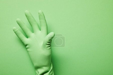 Photo for Cropped view of man in rubber glove on green background - Royalty Free Image