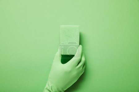 Photo pour Vue recadrée de l'homme en gant de caoutchouc tenant éponge verte - image libre de droit