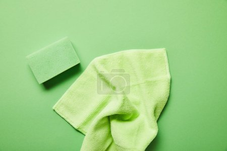 top view of colorful rag and sponge on green background