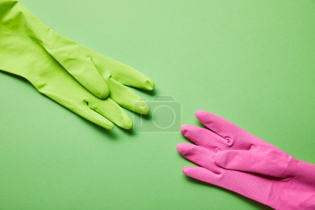 Photo for Top view of bright and colorful rubber gloves on green background - Royalty Free Image