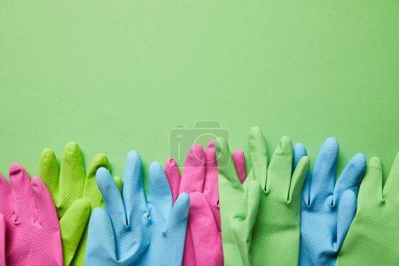 Photo pour Vue supérieure des gants en caoutchouc colorés et lumineux sur le fond vert - image libre de droit