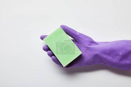 Photo pour Vue recadrée de l'homme dans le gant en caoutchouc pourpre retenant l'éponge verte - image libre de droit