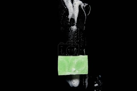 top view of green and colorful sponge with foam on black background