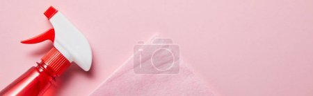 Photo pour Plan panoramique de chiffon pastel et bouteille avec vaporisateur sur fond rose - image libre de droit