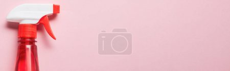 Photo for Panoramic shot of red bottle with spray on pink background - Royalty Free Image