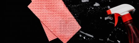 vue du dessus de chiffon rose et bouteille avec pulvérisation sur fond noir