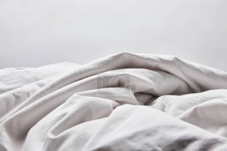 Photo for Crumpled white blanket in bed isolated on grey - Royalty Free Image