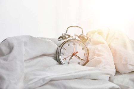 Foto de Reloj despertador de plata en la manta en la cama blanca con la luz del sol en el fondo - Imagen libre de derechos