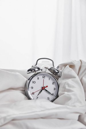 Photo for Silver alarm clock in blanket in white bed - Royalty Free Image