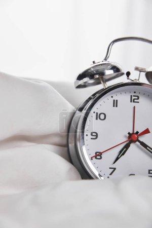Foto de Vista de cerca del reloj despertador de plata en la cama blanca - Imagen libre de derechos
