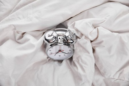 Photo for Top view of silver alarm clock in white bed - Royalty Free Image