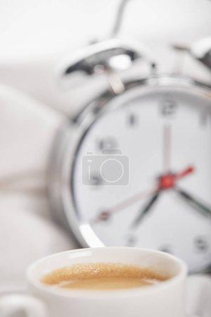 Photo pour Foyer sélectif du café dans la tasse blanche avec le réveil argenté dans le lit sur le fond - image libre de droit