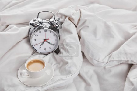 Photo for Coffee in white cup on saucer near silver alarm clock in bed - Royalty Free Image