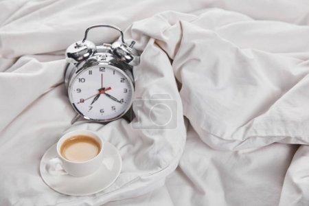 Photo pour Café en tasse blanche sur soucoupe près d'un réveil en argent au lit - image libre de droit