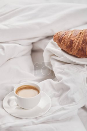 Photo for Fresh tasty croissant on plate near coffee in white cup on saucer in bed - Royalty Free Image