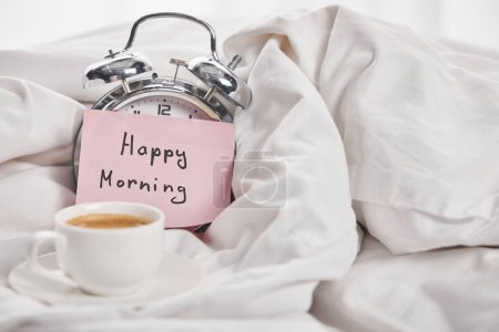 Photo for Coffee in white cup near silver alarm clock with happy morning lettering on sticky note in bed - Royalty Free Image