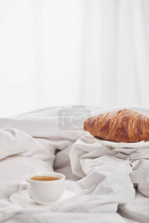 Photo for Delicious croissant on plate near coffee in white cup on saucer in bed - Royalty Free Image