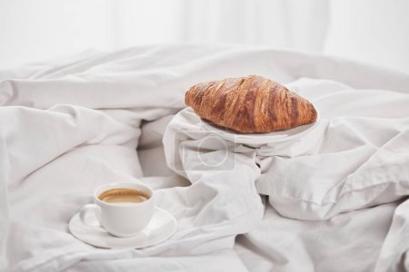 Photo for Tasty croissant on plate near coffee in white cup on saucer in bed - Royalty Free Image