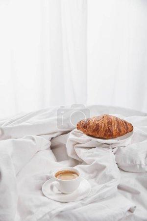 Photo pour Croissant frais sur assiette près de café en tasse blanche sur soucoupe au lit - image libre de droit