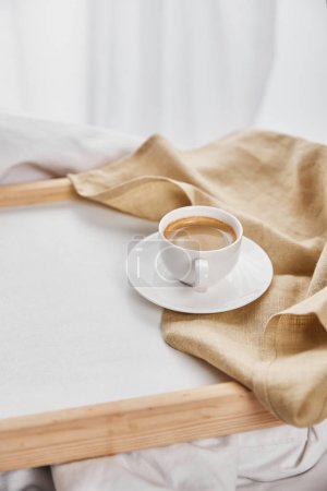 Photo for Coffee in white cup on saucer near beige napkin on wooden tray - Royalty Free Image