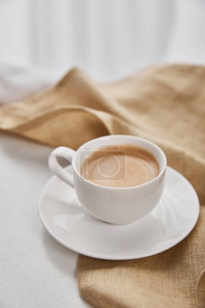 Photo for Close up view of coffee in white cup on saucer near beige napkin - Royalty Free Image