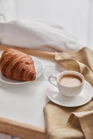 Photo for Fresh croissant on plate with coffee in cup on wooden tray in bed at morning - Royalty Free Image