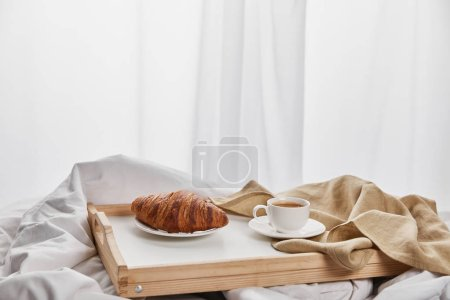Photo for Fresh croissant with coffee in cup on wooden tray in bed at morning - Royalty Free Image