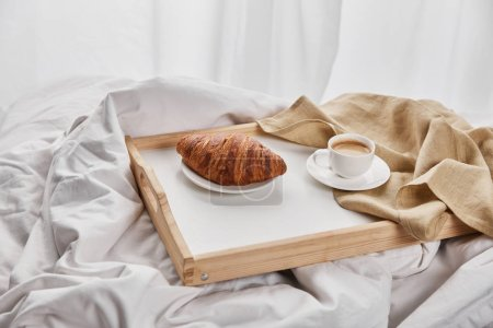 Photo for Fresh croissant with coffee and napkin on wooden tray in bed at morning - Royalty Free Image