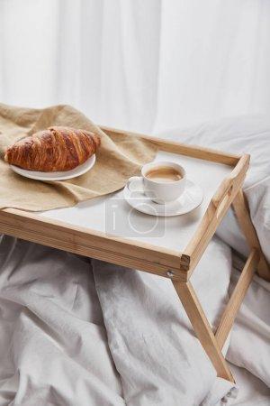 Foto de Croissant fresco con café en bandeja de madera en la cama por la mañana - Imagen libre de derechos