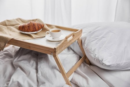 Photo for Fresh croissant with coffee on wooden tray in bed with pillow at morning - Royalty Free Image