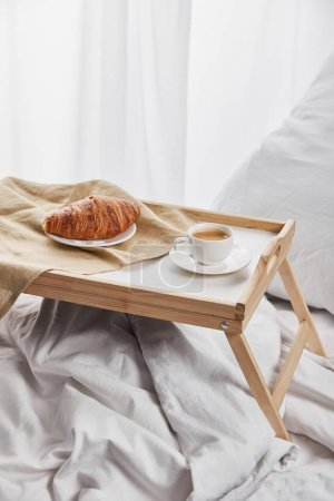 Photo for Coffee and croissant served on wooden tray on white bed with pillow - Royalty Free Image