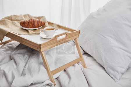 Photo for Coffee and croissant served on wooden tray on white bedding - Royalty Free Image