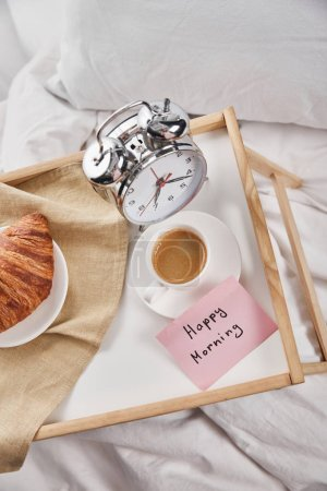 Photo pour Vue supérieure du réveil, note collante avec le lettrage heureux de matin, café et croissant sur le plateau en bois sur la literie blanche - image libre de droit
