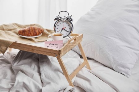 alarm clock, sticky note with happy morning lettering, coffee and croissant on wooden tray on white bedding