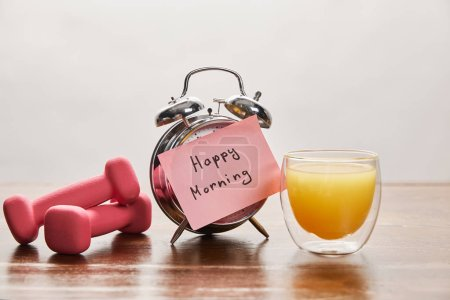 Photo for Silver alarm clock with happy morning lettering on pink sticky note near pink dumbbells and orange juice on wooden table isolated on grey - Royalty Free Image
