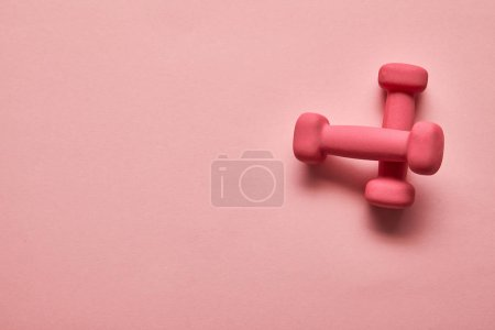 Photo for Top view of pink dumbbells on pink background with copy space - Royalty Free Image