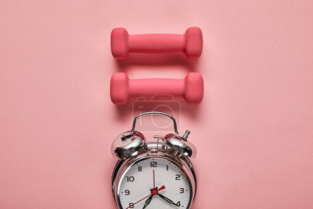 Photo for Flat lay with silver alarm clock and pink dumbbells on pink background - Royalty Free Image