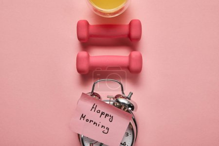 Photo for Flat lay with happy morning lettering on silver alarm clock, pink dumbbells and orange juice on pink background - Royalty Free Image