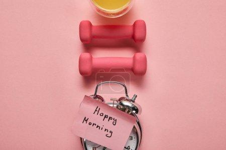 Foto de Estaba plana con letras de la mañana feliz en el reloj despertador de plata, mancuernas rosas y jugo de naranja sobre fondo rosa - Imagen libre de derechos